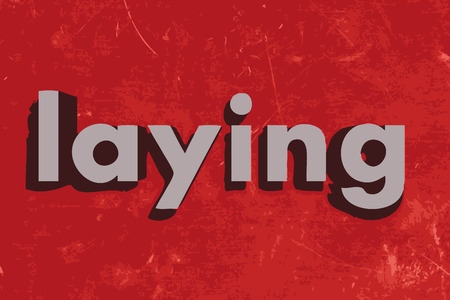 laying: laying word on red concrete wall