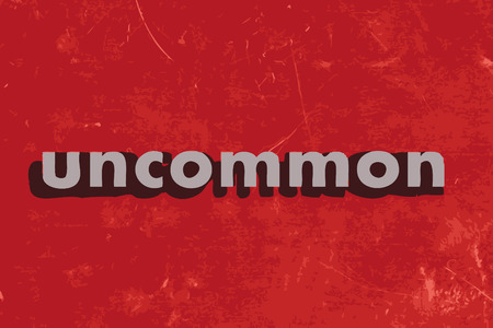 uncommon: uncommon vector word on red concrete wall
