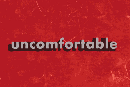 uncomfortable: uncomfortable vector word on red concrete wall