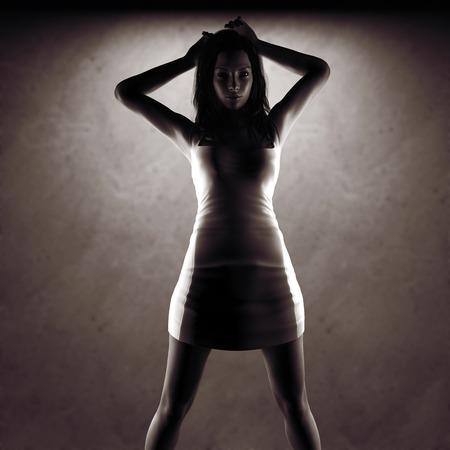 black fashion model: sexy woman in dress posing near stone wall