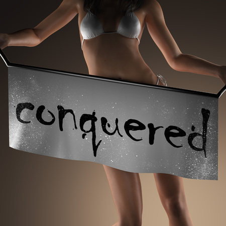 conquered: conquered word on banner and bikiny woman Stock Photo