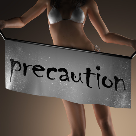 precaution: precaution word on banner and bikiny woman Stock Photo