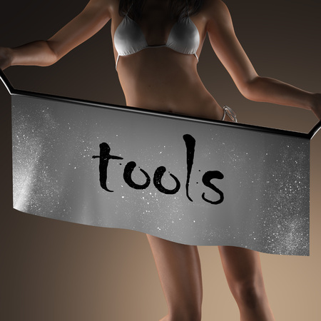 modelos posando: tools word on banner and bikiny woman Foto de archivo