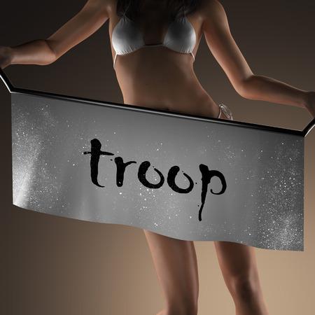 troop: troop word on banner and bikiny woman