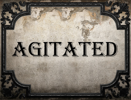 agitated: agitated word on concrette wall Stock Photo