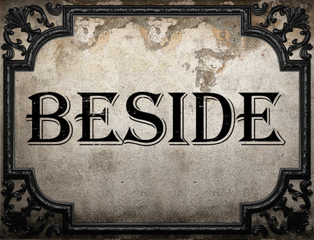 beside: beside word on concrette wall Stock Photo
