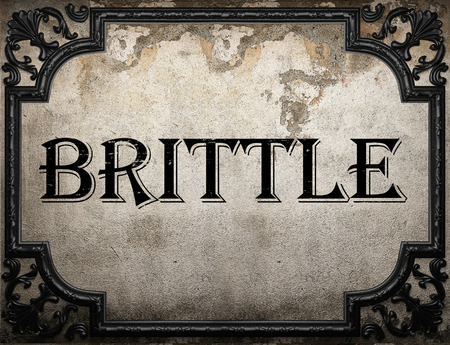 brittle: brittle word on concrette wall Stock Photo