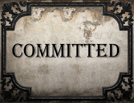 committed: committed word on concrette wall Stock Photo