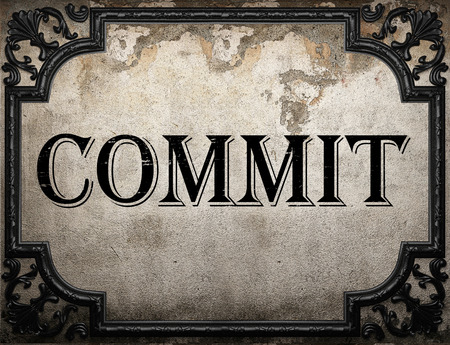 to commit: commit word on concrette wall Stock Photo