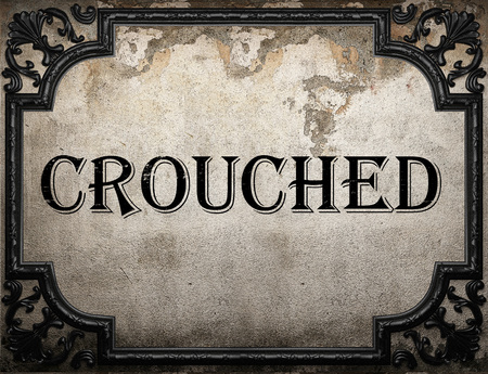 crouched: crouched word on concrette wall Stock Photo