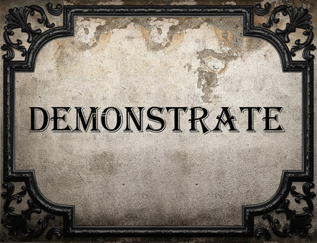 demonstrate: demonstrate word on concrette wall Stock Photo