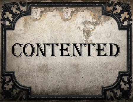 contented: contented word on concrette wall Stock Photo