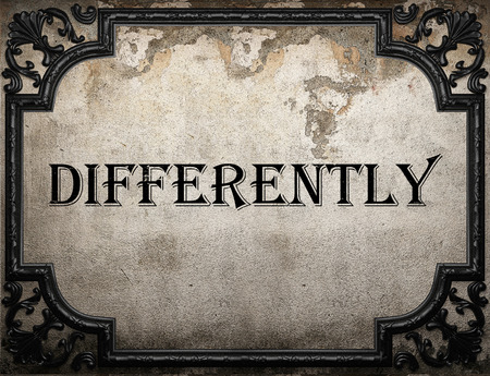 differently: differently word on concrette wall Stock Photo
