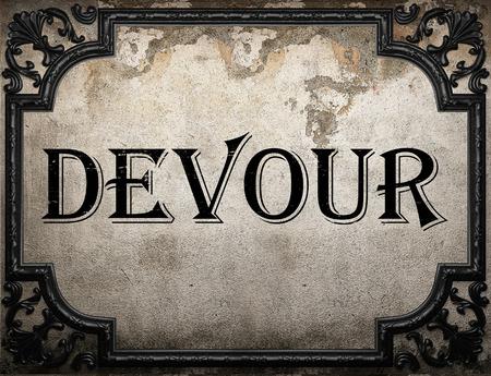 devour: devour word on concrette wall Stock Photo