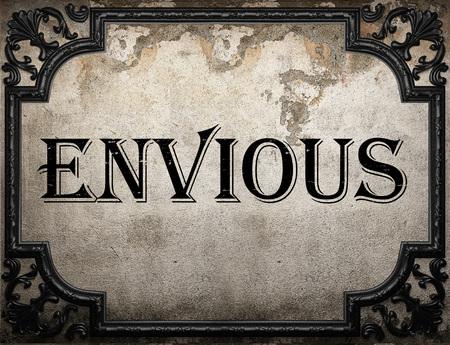 envious: envious word on concrette wall Stock Photo
