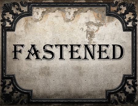 fastened: fastened word on concrette wall Stock Photo