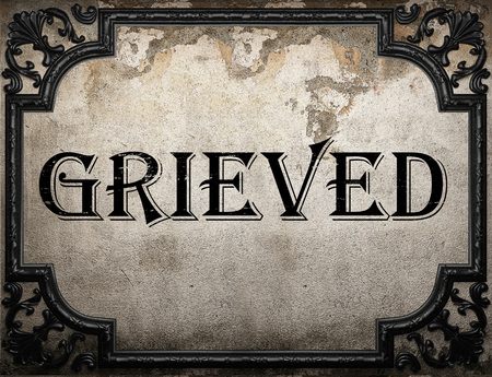 grieved: grieved word on concrette wall Stock Photo