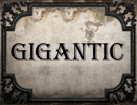 gigantic: gigantic word on concrette wall Stock Photo