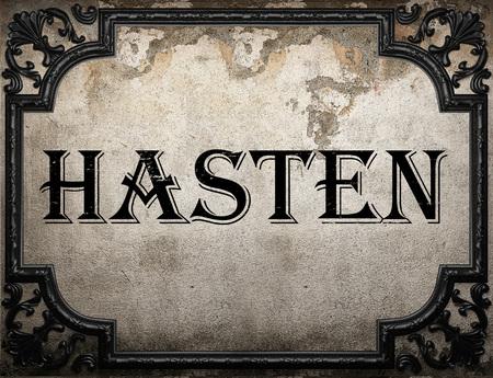 to hasten: hasten word on concrette wall Stock Photo