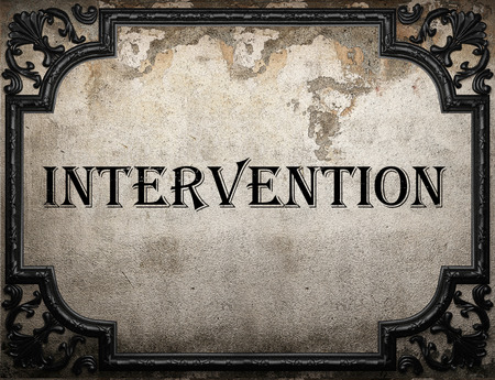 intervention: intervention word on concrette wall Stock Photo