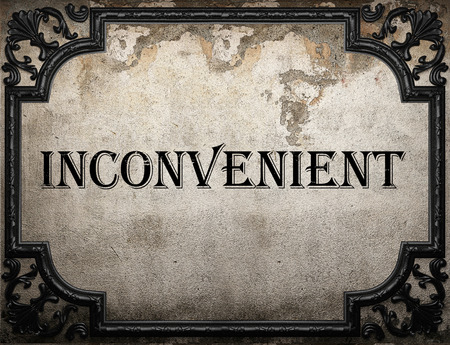 inconvenient: inconvenient word on concrette wall