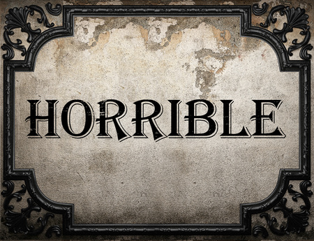 horrible: horrible word on concrette wall Stock Photo