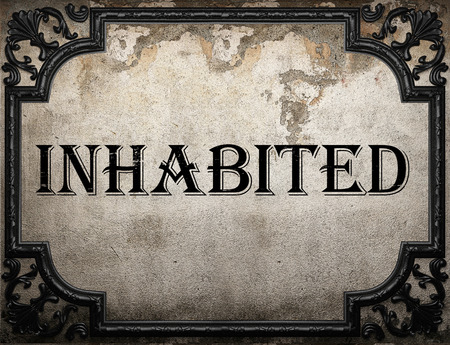 inhabited: inhabited word on concrette wall
