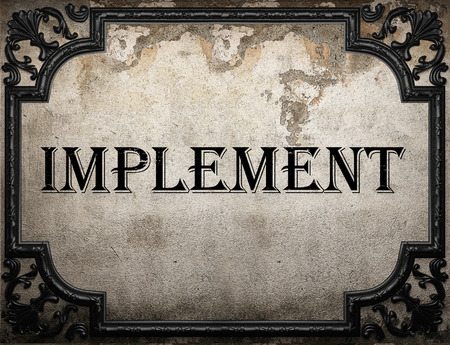 implement: implement word on concrette wall Stock Photo
