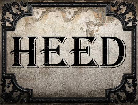 heed: heed word on concrette wall Stock Photo