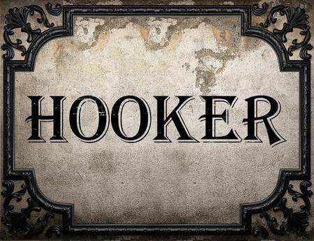 hooker: hooker word on concrette wall Stock Photo