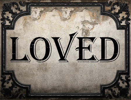 loved: loved word on concrette wall Stock Photo