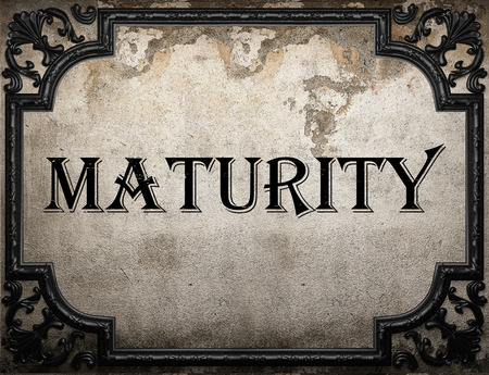 maturity: maturity word on concrette wall Stock Photo