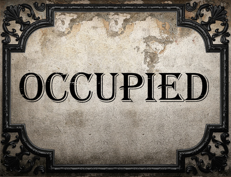 occupied: occupied word on concrette wall