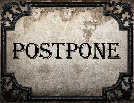 postpone: postpone word on concrette wall Stock Photo