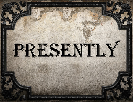 presently: presently word on concrette wall Stock Photo