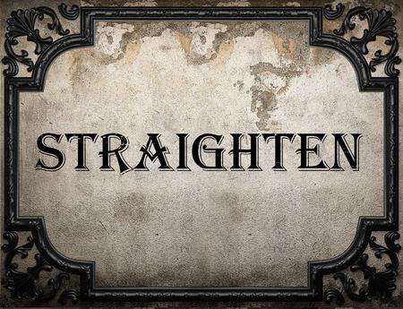 straighten: straighten word on concrete wall Stock Photo