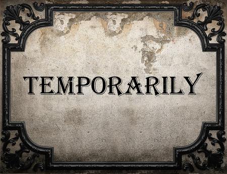 temporarily: temporarily word on concrete wall Stock Photo