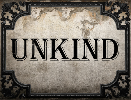 unkind: unkind word on concrete wall