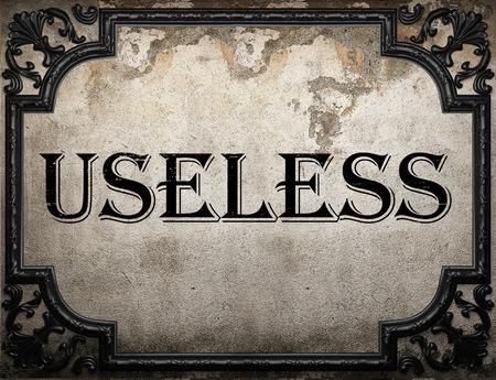 useless: useless word on concrete wall