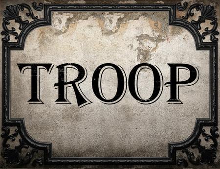 troop: troop word on concrete wall