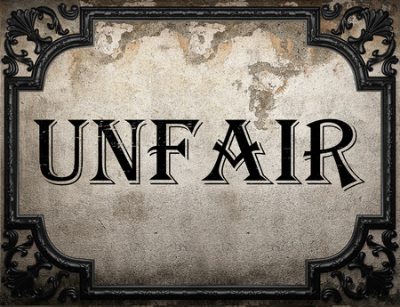 unfair: unfair word on concrete wall