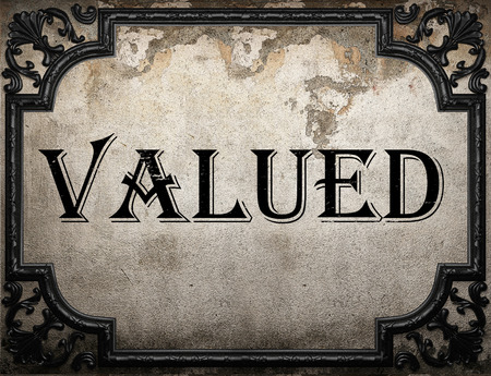 valued: valued word on concrete wall Stock Photo
