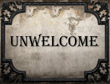 unwelcome: unwelcome word on concrete wall