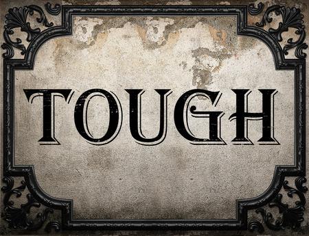 tough: tough word on concrete wall