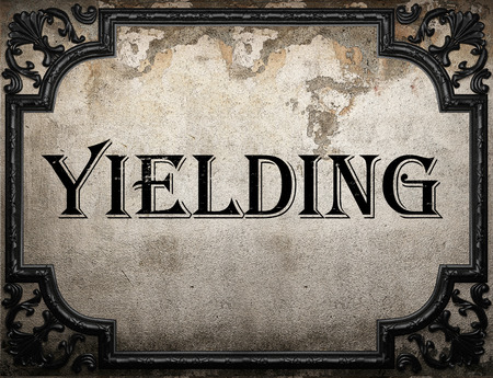 yielding: yielding word on concrete wall