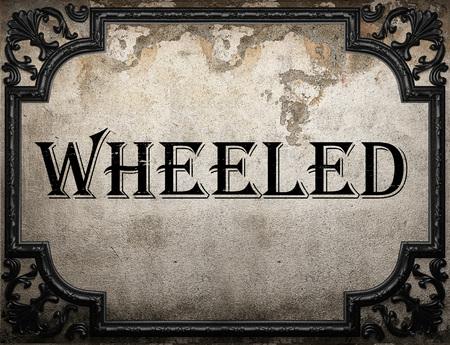 wheeled: wheeled word on concrete wall Stock Photo
