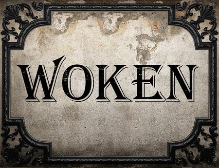 woken: woken word on concrete wall