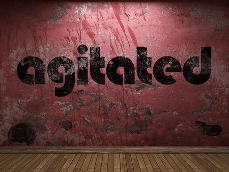 agitated: agitated word on red wall Stock Photo
