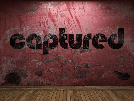 captured: captured word on red wall Stock Photo
