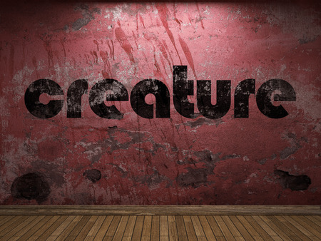 creature: creature word on red wall Stock Photo